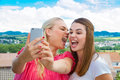 Funny selfie girlfriends with smartphone on the terrace Royalty Free Stock Images