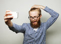Funny selfie happy day life style concept a young man with a beard in shirt holding mobile phone and making photo of himself while Stock Photography