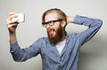 Funny selfie happy day life style concept a young man with a beard in shirt holding mobile phone and making photo of himself while Stock Photos