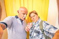 Funny senior happy couple taking a selfie while eating granita crushed ice cream concept of youthful active elderly and Stock Photos