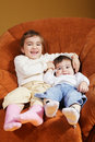 Funny sisters sitting in chair Stock Photos