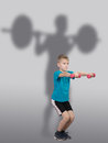 Funny slim ten year old boy doing squat exercises with weightlifter s silhouette behind him on grey background Royalty Free Stock Photos