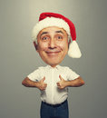 Funny smiley senior man in red santa hat showing thumbs up over grey background Stock Image