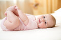 Funny smiling baby infant girl playing with her feet Royalty Free Stock Photo