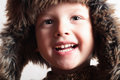 Funny smiling child in a fur hat fashion kid winter style little boy children portrait of Royalty Free Stock Photography