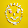 Funny smily face made of chewing gums round different mint candies and drops on bright yellow background Stock Images