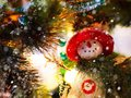 Funny snowman in a red hat and green scarf on the background of Christmas tree branches with lights