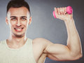 Funny sporty fit man lifting light dumbbell. Fun. Royalty Free Stock Photo