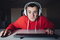 Funny teenager In the evening enjoy a home computer. The guy looks closely at the monitor. Looking into the camera. Royalty Free Stock Photo