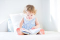 Funny toddler girl in a blue dress reading book Royalty Free Stock Photo