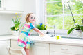 Funny toddler girl in colorful dress washing dishes cute curly a cleaning with a sponge and playing with foam the sink a beautiful Royalty Free Stock Image