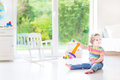 Funny toddler girl with pyramid toy in white room Royalty Free Stock Photo