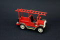 Funny vintage toy fire truck made ​​of plastic on a dark background Stock Images
