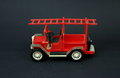Funny vintage toy fire truck made of plastic on a dark background Royalty Free Stock Photography