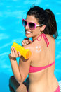 Funny woman applying sunscreen on summer or suntan lotion her back and sitting at poolside holidays skin care and protection Stock Photos
