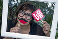 Funny woman frame mustache love spectacles with crooked eyes wearing heart shaped holding fake lips and and signpost inside Royalty Free Stock Photography