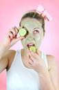 Funny woman with green facial mask eating cucumber cheerful young wearing a is biting into a slice of pink background Stock Photos