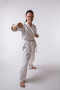 Funny woman in kimono on white show punch martial art exercise Stock Photography