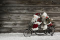 Funny wooden christmas background with two santa claus on a bicy bicycle making xmas shopping also witty concept for teamwork Stock Photo