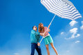 Funny and young couple have fun with beach umbrella on blue sky background Stock Image