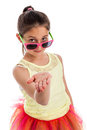 Funny young girl with hand out flat quirky colourful cloths holding her wearing sun glasses and looking to camera isolated on Royalty Free Stock Photo