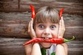 Funny young girl with a red hot chili pepper in her mouth showing red devil horns Royalty Free Stock Images