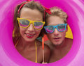 Funny young happy beach couple smiling  in the middle of pink inflatable ring. Royalty Free Stock Photo