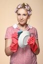 Funny young housewife with gloves holding scrubberr Stock Photo