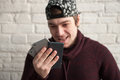 Funny young man in a cap and sweater is holding three smartphones in his hand Royalty Free Stock Photo