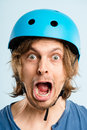 Funny young man wearing cycling helmet looking shocked Royalty Free Stock Photos