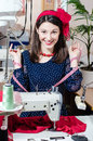 Funny young pinup pretty woman in polka dot dress with sewing machine and measuring tape happy smiling looking at camera portrai Stock Images