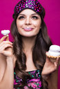 Funny young woman in sleeping mask and pajamas, sweets on pink background. beauty face. Royalty Free Stock Photo