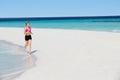 Funzionamento della donna sulla bella spiaggia Fotografia Stock