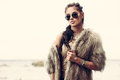 Fur coat and flash tattoos portrait of a beautiful lady with tottoos posing outdoors near the sea Stock Photo