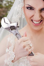 Furious bride holding wrench Royalty Free Stock Photos