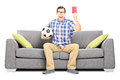 Furious football fan on sofa holding ball and giving a red card young sitting isolated white background Stock Photo