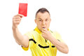 Furious football referee showing a red card and blowing whistle isolated on white background Stock Image