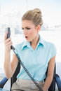Furious stylish businesswoman shouting on the phone in bright office Royalty Free Stock Photo