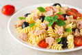 Fusilli pasta salad with tuna, tomatoes, black olives and basil on gray stone background Royalty Free Stock Photo