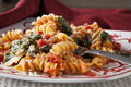 Fusilli pasta with tomatos and fresh baby spinach a red white plate filled prepared diced parmesan cheese Stock Image