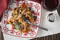 Fusilli pasta with tomatos and fresh baby spinach a red white plate filled prepared diced parmesan cheese a glass of red Royalty Free Stock Photography