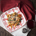 Fusilli pasta with tomatos and fresh baby spinach a red white plate filled prepared diced parmesan cheese a glass of red Royalty Free Stock Photos