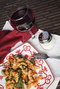 Fusilli pasta with tomatos and fresh baby spinach a red white plate filled prepared diced parmesan cheese a glass of red Stock Image