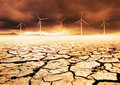 Future farm wind turbines on a cracked earth desert Stock Photos