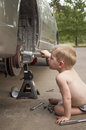 Future mechanic little boy works on fixing a car Stock Photos