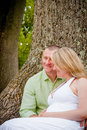 Future parents happy together young men and women soon to be sitting under a tree in a park woman is pregnant Royalty Free Stock Images