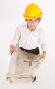 Future professional young boy wearing a safety helmet holding architecture blueprints Royalty Free Stock Photography