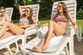 Fyra vänner solbadar på soldagdrivarna på stranden Royaltyfri Fotografi