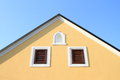 Gable house yellow small windows and blue sky behind Royalty Free Stock Image