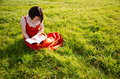 Gaining knowledge in nature a young woman a traditional style dress reading a book and surrounded by grass on a sunny day Stock Photography